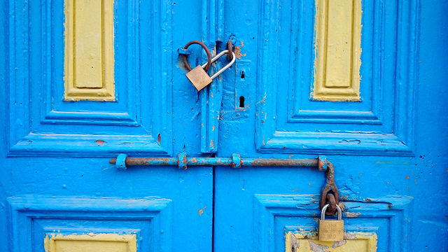 An old-fashioned blue door with a locked padlock.